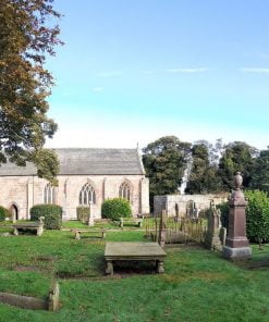 A graveyard with many monuments and gravestones occupies the foreground. Two large deciduous trees are to the left. Centre background is the sidewall of a smallish church building dating from the 14th century. The door is to the left hand end, and three gothic arched windows occupy the rest of the wall. There are bushes and trees behind it, and a blue sky above.