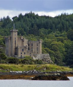 The grey harling towers of Dunvegan Castle are central in this picture. The picture is taken from the boat trip, so there is calm sea in the foreground. Then the castle on its rock, and in the background a hill clad in dark green conifers.