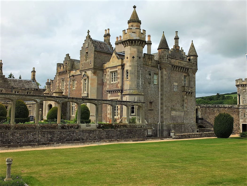 An early 1800's mansionhouse in Scots Baronial Style, this building has green lawns in front of it and a cloudy sky above. There are many pepperpot towers and crow-stepped gables.