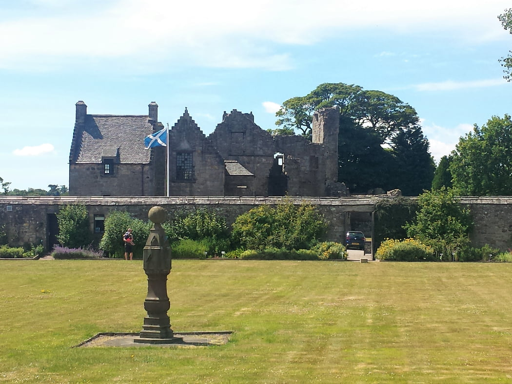 Aberdour Castle is shown here, on the St Andrews, Castles and Golf Tour, as seen on a sunny day from the walled garden. The garden is predominantly mown grass, but with beautiful shrubs around the perimeter against the wall. The 1100's castle and a waving Scottish Flag rise above the garden wall into a bright, white sky.