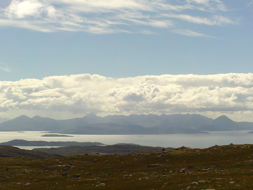This is the view from the top of the NC500 Applecross road, which we visit along with Eilean Donan Castle. From the top of the pass rough boulder-littered ground slopes down towards the sea, two thousand feet below. The sea is a silver blue channel dotted with the silhouettes of small islands, and in the background the many blue peaks of Skye rear towards a great bank of fluffy white clouds above which all is blue. ,