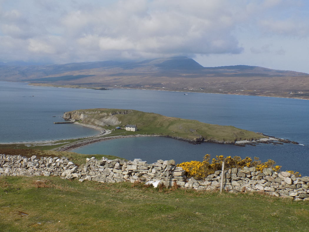 We stand on a grassy rise, looking over a dry-stone wall, two or three hundred feet above a blue sea inlet. On the distant side of the sea inlet are tiny white shapes of a line of cottages, above which grey mountains rise into cloud. Below us, from this shore, a narrow spit of grass and shingle connects the shore with a grassy rocky bluff that would otherwise be an island. On that bluff there are signs of historical quarrying, a pier, an old stone building and a single white two storey house.