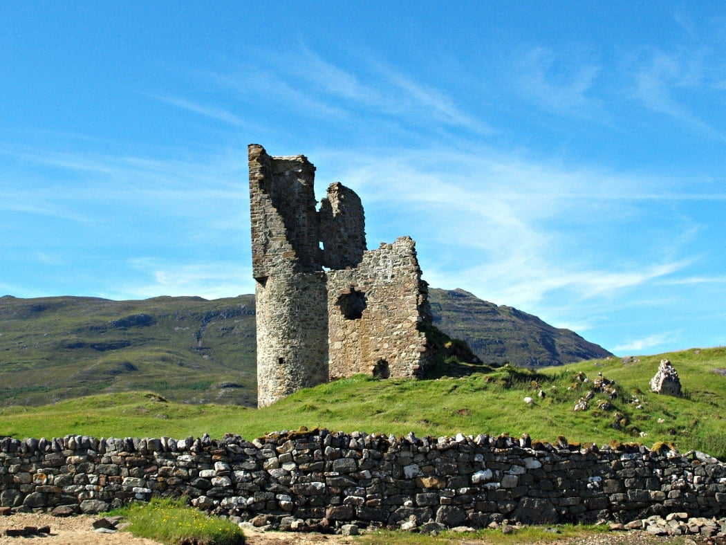 The foreground is a dry-stone wall. On a grassy knoll behind the wall stand the ruins of Ardvreck Castle. Behind that is a distant, rugged brown mountain. Above is a blue sky.