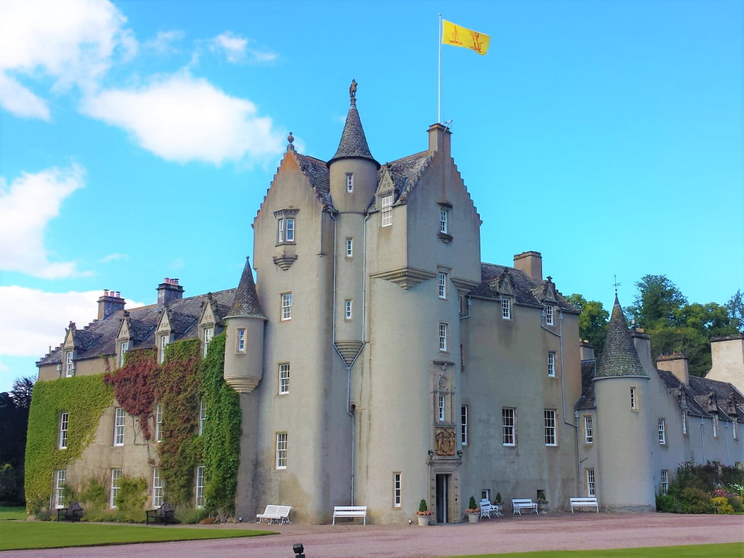Ballindalloch Castle on the Ballindalloch Castle and Speyside Tour Ballindalloch Castle on the North East 250 Tour fills this picture from side to side. It is a lived-in castle from 1500's, finished in a delicate pink harling. It's yellow flag flies from the top of the five-storey tower.