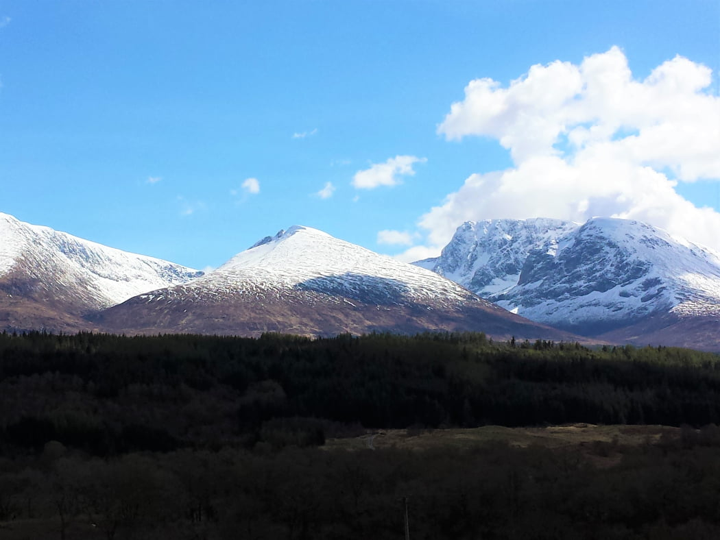 Ben Nevis on our West Coast and Highland Distillery Tour is the rightmost of the three snow covered mountains that fill most of this picture. Above is a blue sky with a few white clouds. in the foreground is a long left-to-right ridge covered in trees mostly (but not exclusively) pine.