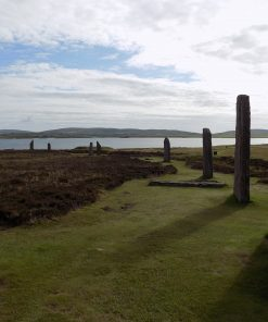 Curving line of standing stones at the Ring of Brodgar on our Orkney - Three Day Tour. The Stones are arising from grass, but otherwise surrounded by heather. The sky above is cloudy blue, and the Loch of Harray is in the background.