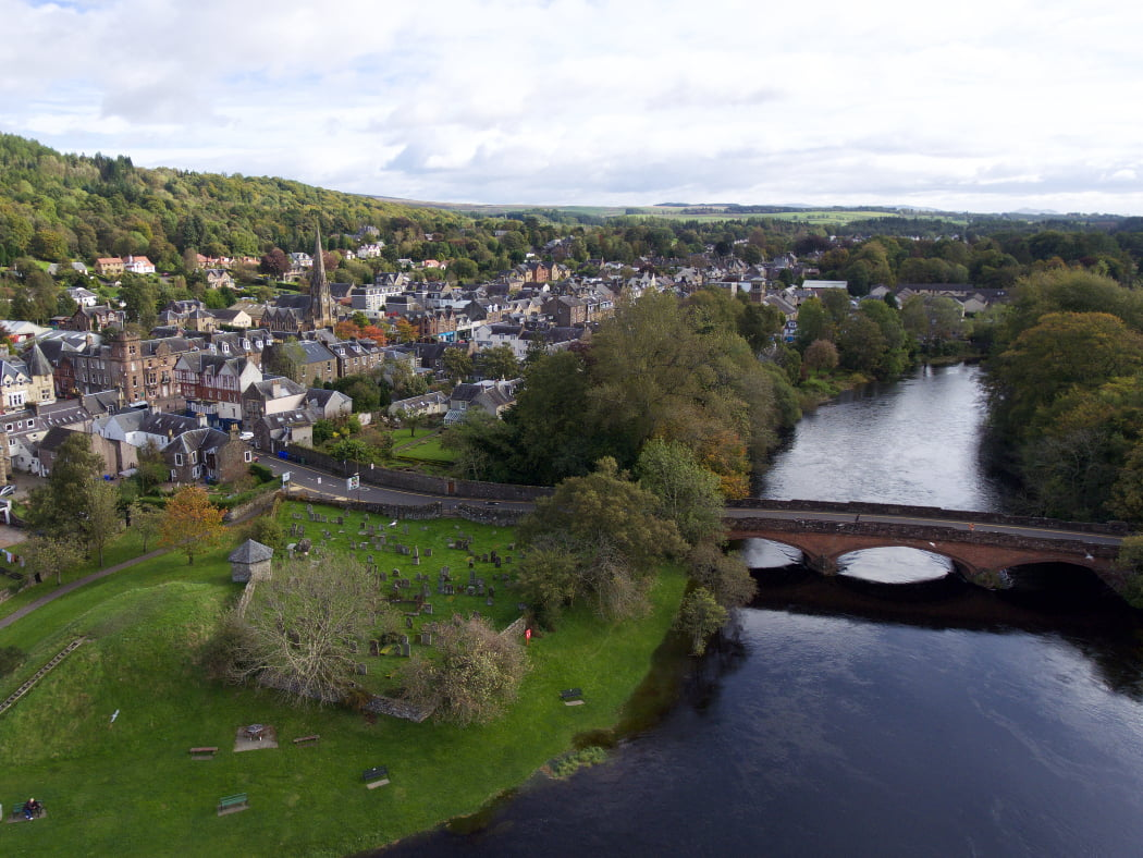 Arial view of a river flowing into picture up the right hand-side, crossed by a three arched bridge from right to left. A small town stands on the left bank, with an old burying ground on green sward on the riverbank. A wooded hill rises to the left and the sky is white.