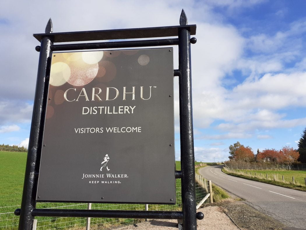 A large grey sign occupies two thirds of this picture. It says Cardhu Distillery, Visitors Welcome. An empty two lane road curves through the fields to the right of the sign.