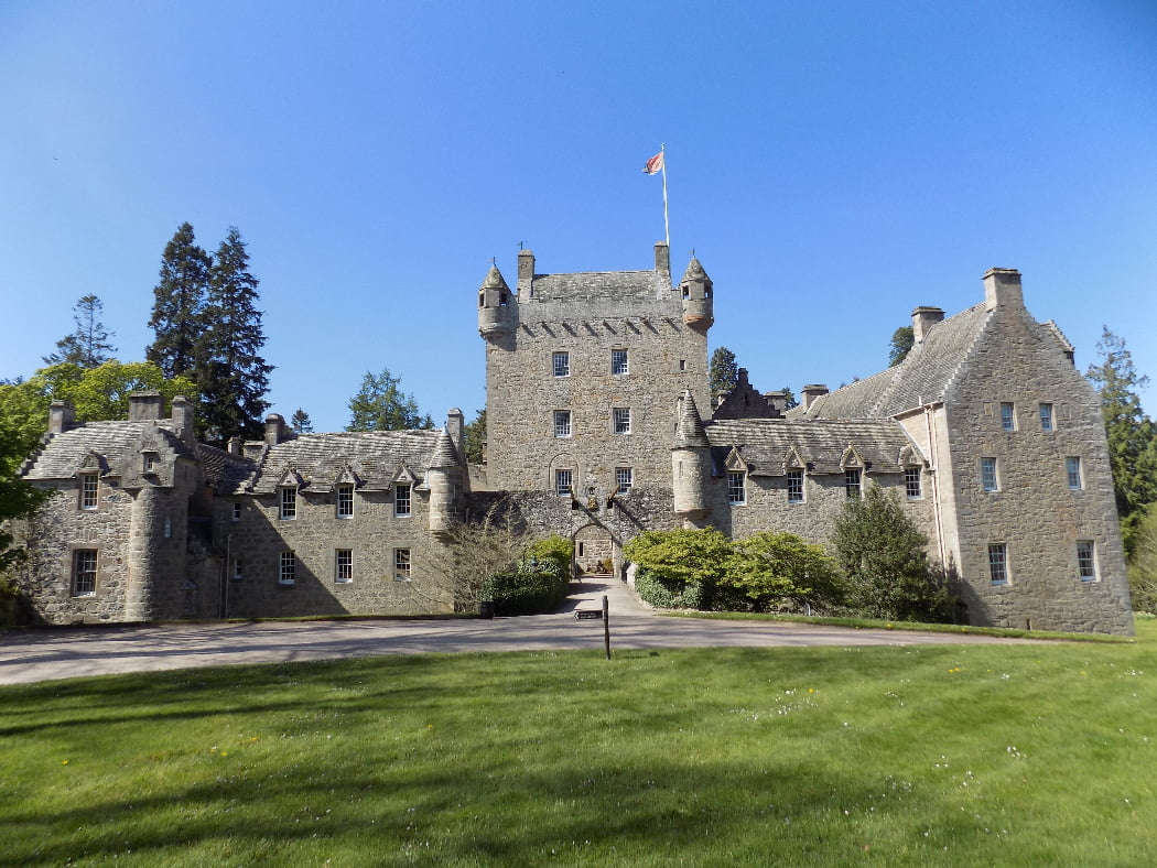 Cawdor Castle fills this image, below a cloudless blue sky on the tour that also visits Culloden and Clava. The castle is grey stone, with green lawns in front, some shrubs either side of the small drawbridge, and large trees behind. The 1300s Keep is square and four storeys high with battlements and a pepper-pot tower at each corner. It is only two windows wide on each side. There are four other wings, in front and to each side, all built of matching stone, but dating from the 1600's, 1700's and 1800's. Although organic, the resulting building is pleasingly consistent and attractive.