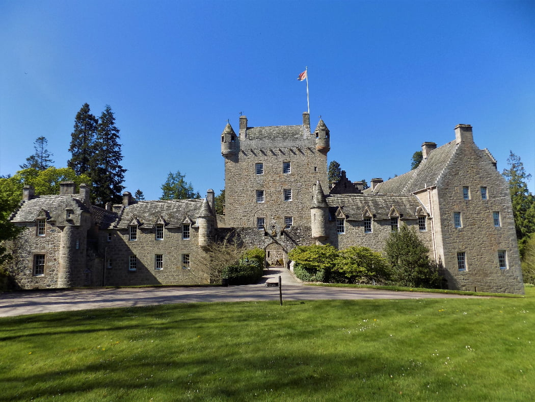 Cawdor Castle fills this image, below a cloudless blue sky. The castle is grey stone, with green lawns in front, some shrubs either side of the small drawbridge, and large trees behind. The 1300s Keep is square and four storeys high with battlements and a pepper-pot tower at each corner. It is only two windows wide on each side. There are four other wings, in front and to each side, all built of matching stone, but dating from the 1600's, 1700's and 1800's. Although organic, the resulting building is pleasingly consistent and attractive.