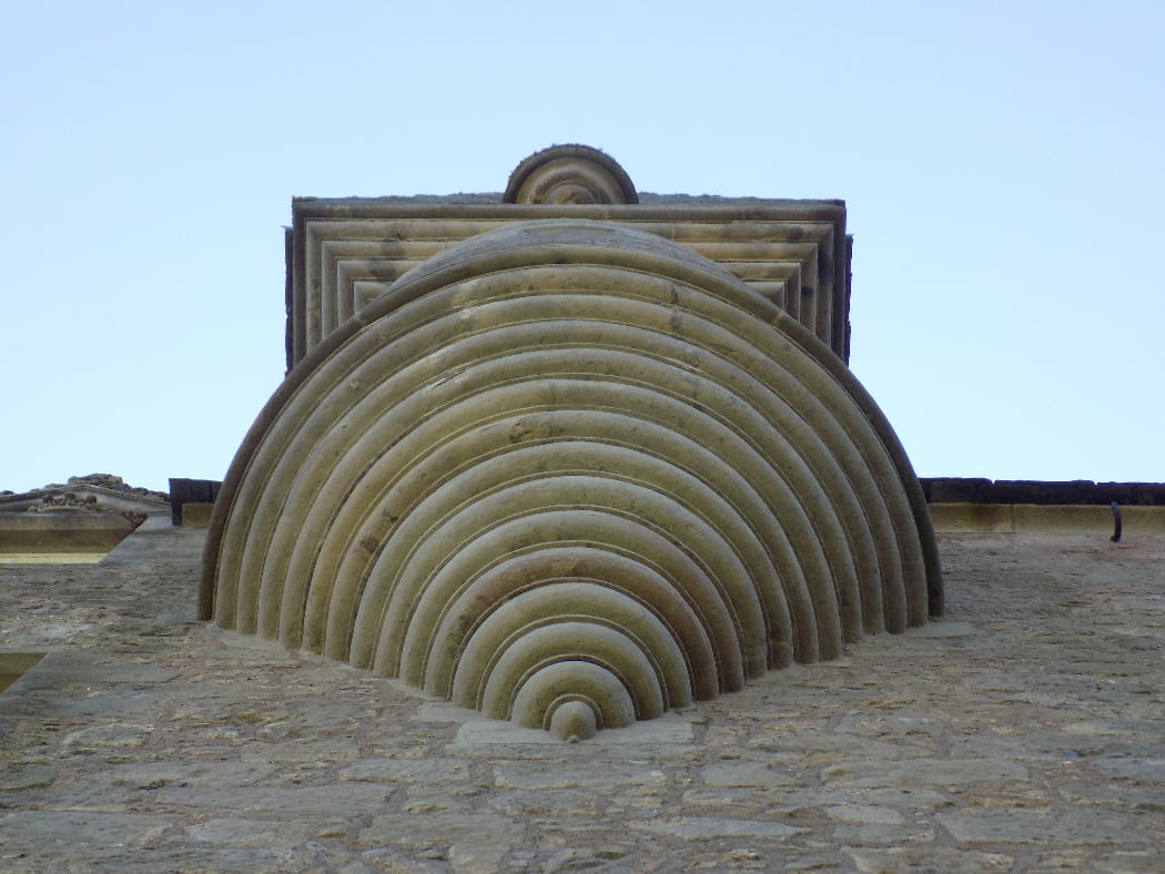 We are standing beneath a tiny turret, made from carved yellow stone. The underside, which is above our heads, is decoratively worked with delicate semi circles increasing in size as it goes upwards. That is where it meets a square stone, also worked with increasing decorative square trim. The sky is cloudless and the palest of blues.