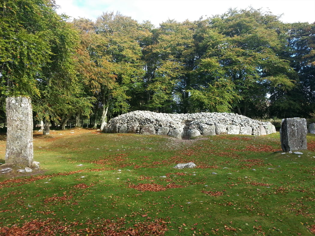 In front of us is a bronze age passage grave. There is grass in the foreground, and two prominent standing stones, one to the extreme left, the other the extreme right. Between and slightly behind them is the roofless cairn, with the mouth of the entry passage towards us. In the background are large, leafy, deciduous trees.