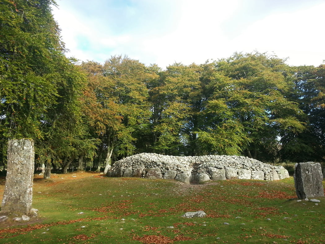 In front of us is the north-east passage grave on the Culloden Battlefield and Clava Cairns Walking Tour. There is grass in the foreground, and two prominent standing stones, one to the extreme left, the other the extreme right. Between and slightly behind them is the roofless bronze age cairn, with the mouth of the entry passage towards us. In the background are large, leafy, deciduous trees.