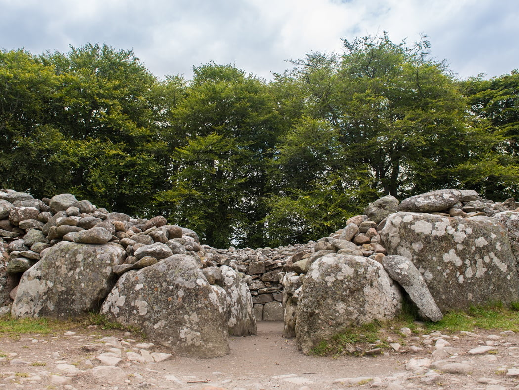 The entire image is a close-up of the bronze age cairn at Clava. The shot is taken from ground level, looking straight in the entry passage from about 6 feet away. The background is entirely filled by mature deciduous trees in leaf, and a little cloudy sky above.