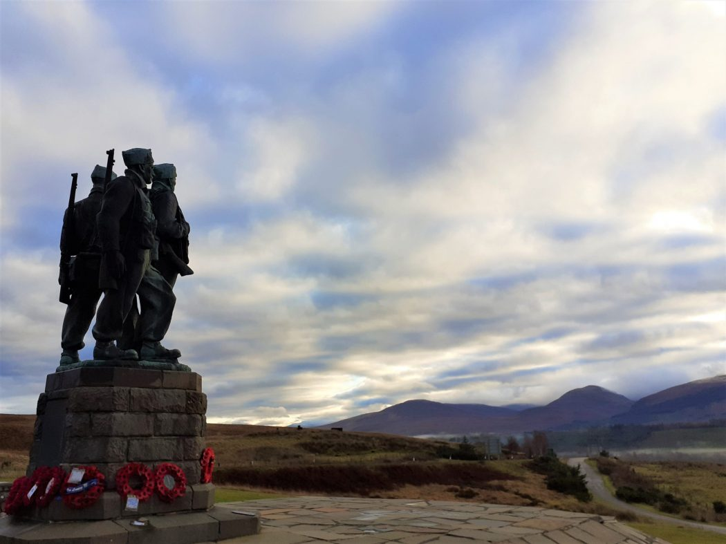 to the left the Commando Memorial is silhouetted against a mottled cloudy and blue sky. The plinth is surmounted by the larger than life figures of three 1940's British Commandos. There are poppy wreaths around the base. There are dark mountains to the right - the direction the figures are looking. A single track road runs away from us, between us and the mountains. - Isle of Mull and Duart Castle Tour