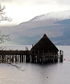 Loch Tay, on our Doune Castle and Highlands Tour, is a still, silvery blue in this shot. Across the water rises the snow-capped bulk of a mountain. In the foreground, silhouetted against the water is an Iron Age hut on a rough log pier or platform. This type of dwelling is known as a Crannog.