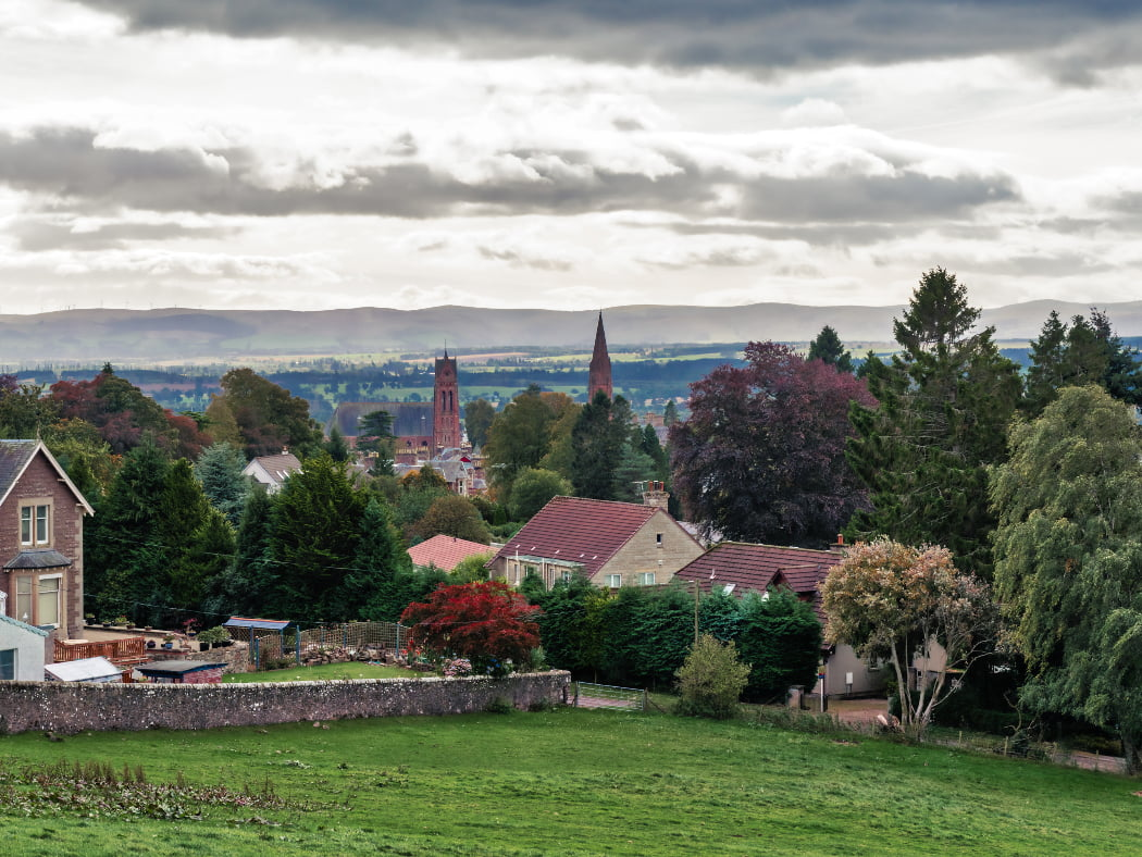 Green grass in the foreground, and then a number of two-storey houses protruding from a tree-filled ladscape. Two church towers rise from the trees in the middle distance and their are fields, woods and low hills in the far distance. The sky is cloudy.Crieff - Stirling Castle and Wallace Monument Tour