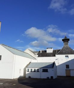 A white painted Scottish whisky distillery, Dallas Dhu, on the Ballindalloch Castle and Speyside Tour. There is a large square brick built chimney to the left, and a building with distillery-style pagoda roof to the right. The sky above is mostly blue, and with some fluffy white clouds.