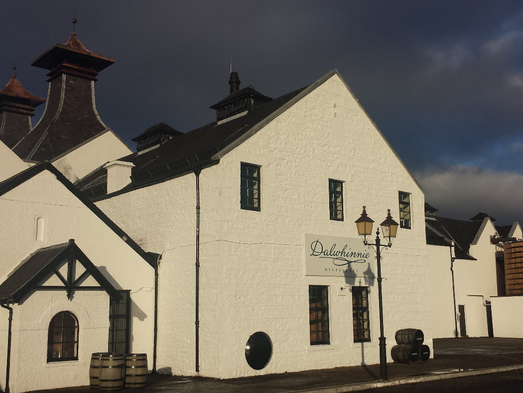 The whole picture is a large white building with two pagoda-style roofs, and a sign that says Dalwhinnie Distillery. There are six barrels, arranged in two sets of three, in front of the building. The very dark sky above is a startling contrast to the white.