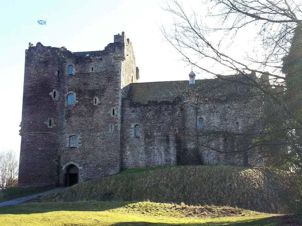 A 1400s castle with four-storey gatehouse at the left, and Great Hall Range to the right. Castle in silhouette, sunshine on the grass in front, a white sky above. The Scottish flag flies from the top of the gatehouse.