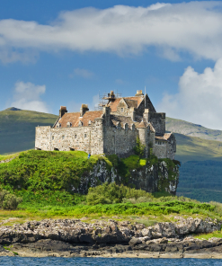 Picture of Duart Castle on the Isle Mull Tour. A typical seaboard stronghold of the Scottish Highlands this was the seat of clan Maclean and dates from the 14th century. The sea is in the foreground, and the castle perches on a rocky bluff above it. A mountain peak rises into a blue sky behind.