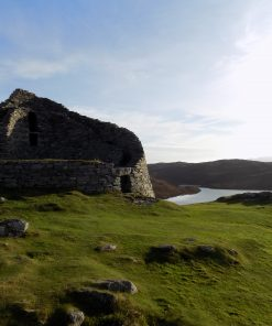A ruined iron age tower called Dun Carloway, on a rocky green hill under a sunny blue sky, with a sea inlet behind. This is visited during both our Hebrides Tours