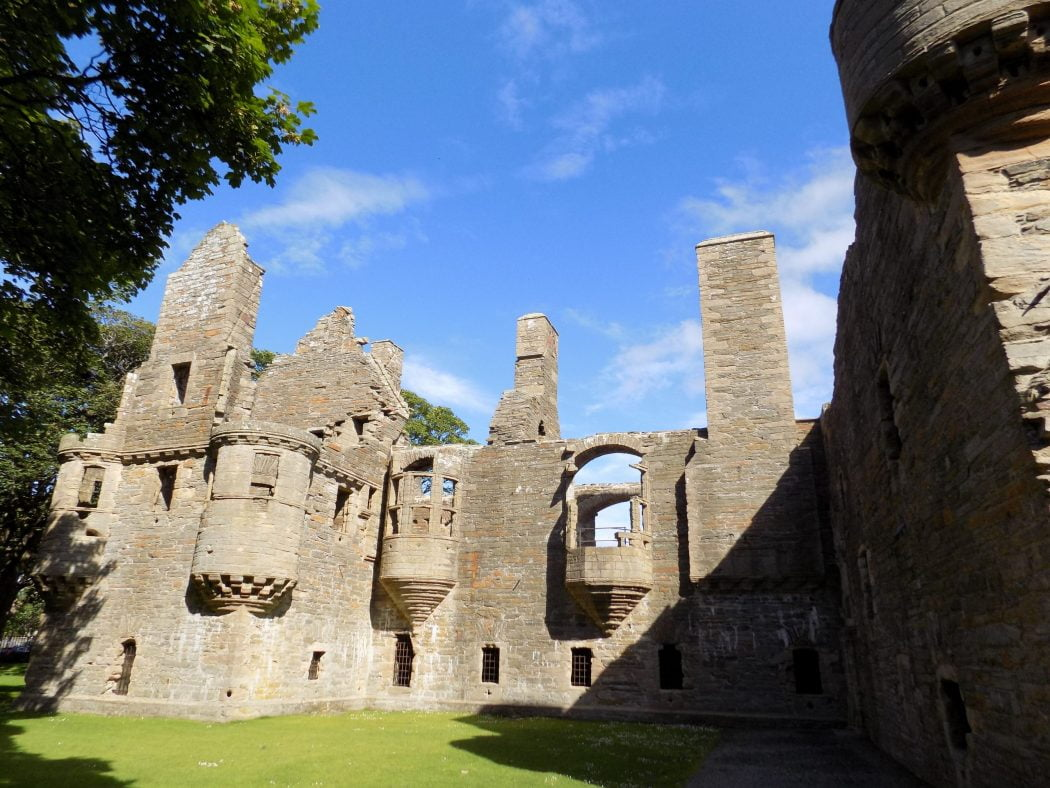 Photograph of the Earls Palace in Kirkwall. This is a ruin dating from the 1600's, photographed in bright sunshine with blue sky above.