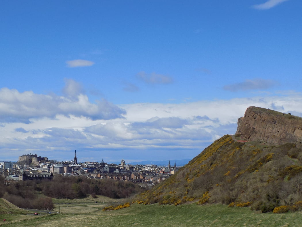 The castle and spires of Edinburgh, on the Outlander Film Locations Tour, are seen in the left-side distance on the horizon. The right side of the image is dominating by the reddish rocks of high crags, the lower slopes of which are covered in yellow flowering gorse. The sky is cloudy and blue.