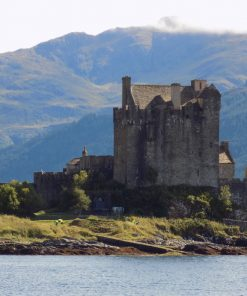 Eilean Donan Castle on the NC500 Applecross tour is across a very narrow arm of the sea. We are nearly at sea level, and a couple of hundred yards away it is built of grey stone rising from a grassy, rocky outcrop. A Scottish Flag flies on a ground mounted flagpole to the left of the castle. A large mountain clothed in coniferous forest rises behind the castle.