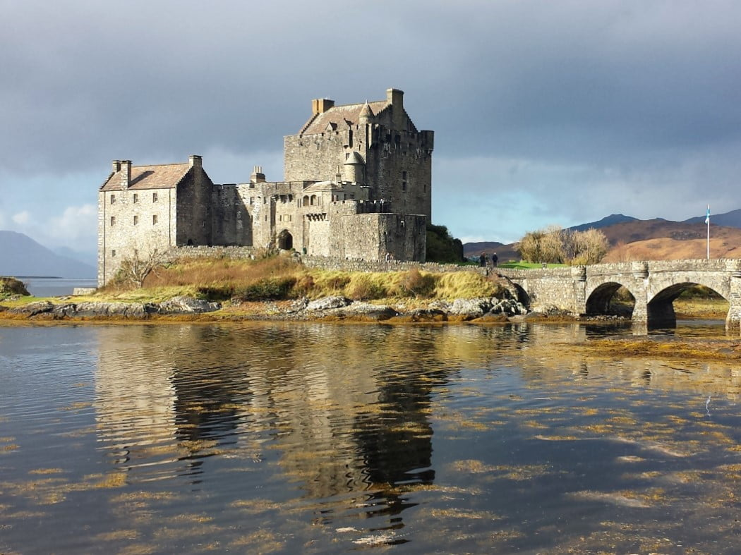 The main area of this picture is the grey Keep of Eilean Donan Castle on an islet, and the arched stone bridge connected it to the mainland exits the frame on the right. The foreground is the slightly rippled reflection of the castle in the sea. The sky above is dark and cloudy.