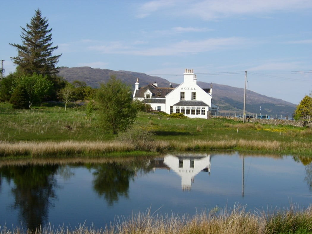 A picturesque traditional white painted building with the word hotel painted on its gable. It stands on grass, and has trees to the left, behind it. The sky is blue and the building is perfectly reflected in a blue pond in the foreground.