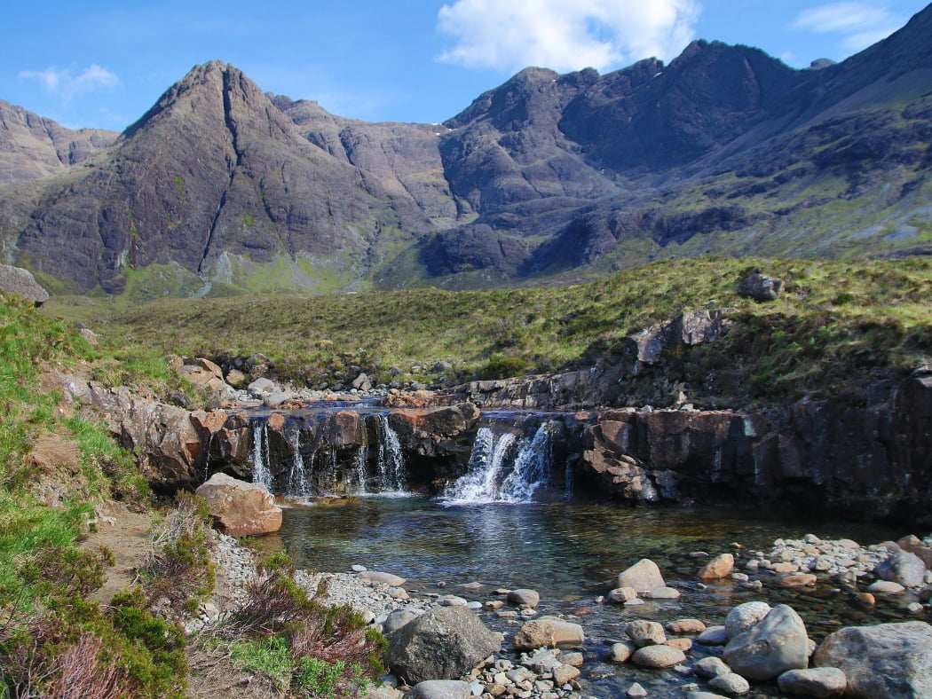 The Fairy Pools, which can be visited on our Isle of Skye Three Day Tour, are shown in this picture. A small river makes a low white-water cascade into a clear pool. Behind are the rocky peaks of the Black Cuillin Mountains. The sky is blue with puffy white clouds.