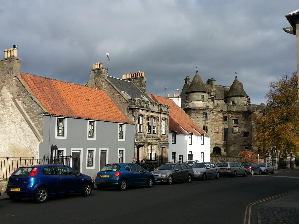 Falkland is a small town on the St Andrews, Castles and Golf Tour. Here are five of the colourful old cottages on the main street. Farther down the street is the 1500's Renaiisance facade of Falkland Palace. The sky is very dark but the buildings are sunlit. There are eight cars parked along the left hand side of the street.