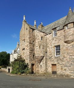 Fordyce Castle, a rustic stone-built Scottish towerhouse fills most of the picture, standing on the village street. To the left is the ancient churchyard beneath a deep blue sky.