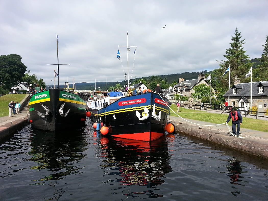 Two brightly painted long canal barges in the waters of a lock gate at Fort Augustus on the Loch Ness and Urquhart Castle Tour. Old village houses can be seen on both banks of the canal, and there are three flags flying outside a house on the right. A man in lifejacket is coiling the rope from the right hand barge around a hook on the ground.