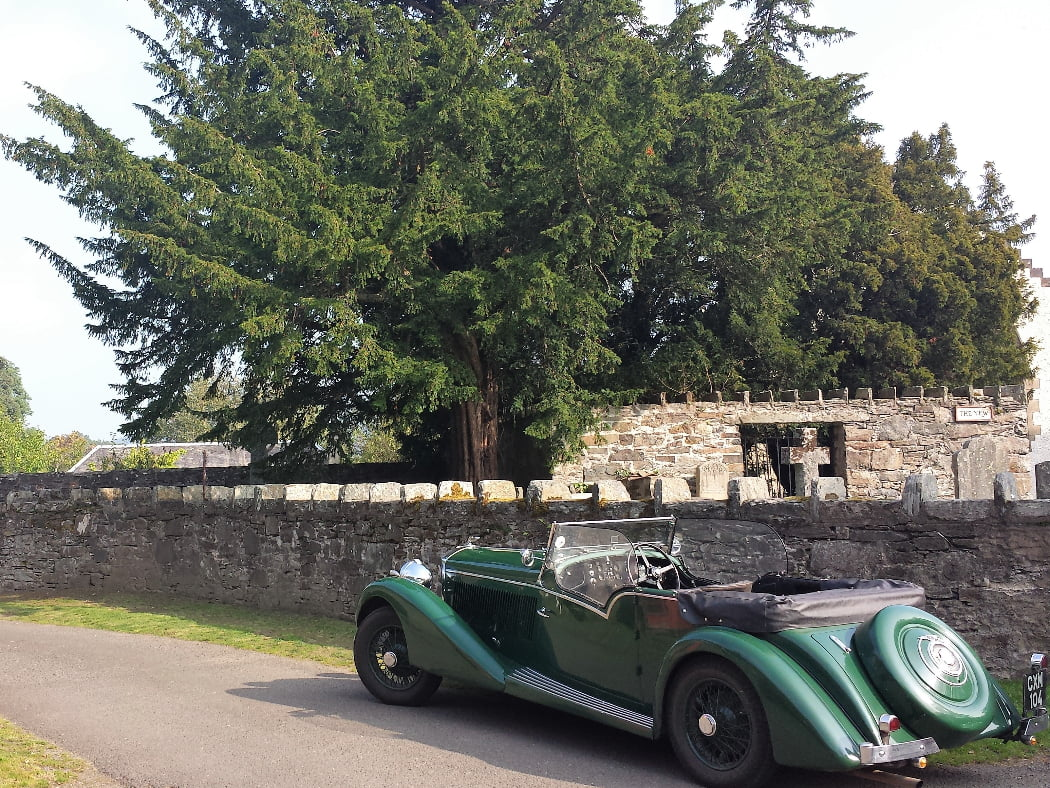 An old green open-topped touring car is parked on the side of a one-track lane with a low stone wall to the right. Over the wall is Fortingall churchyard, a ruined building, and the ancient yew tree.