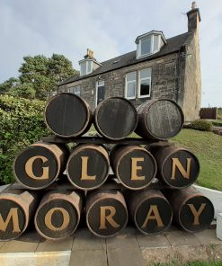 A barrel stack is in front of us. The barrels are on their sides. The top row has three barrels, plain ends. The middle row has four barrels each with a letter on it. The bottom row has five barrels each with a letter on it. The letters spell the words Glen Moray. Behind the barrel stack is a stone built house of two storeys. A door is centrally placed on the ground floor, with a window either side, and two dormer windows above.