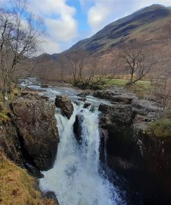 Ariver is flowing towards us down a rugged valley, and cascading over a waterfall just in front of us in the foreground. These Glen Nevis Falls are near the Quidditch stadium site on the Harry Potter in the Highlands Tour