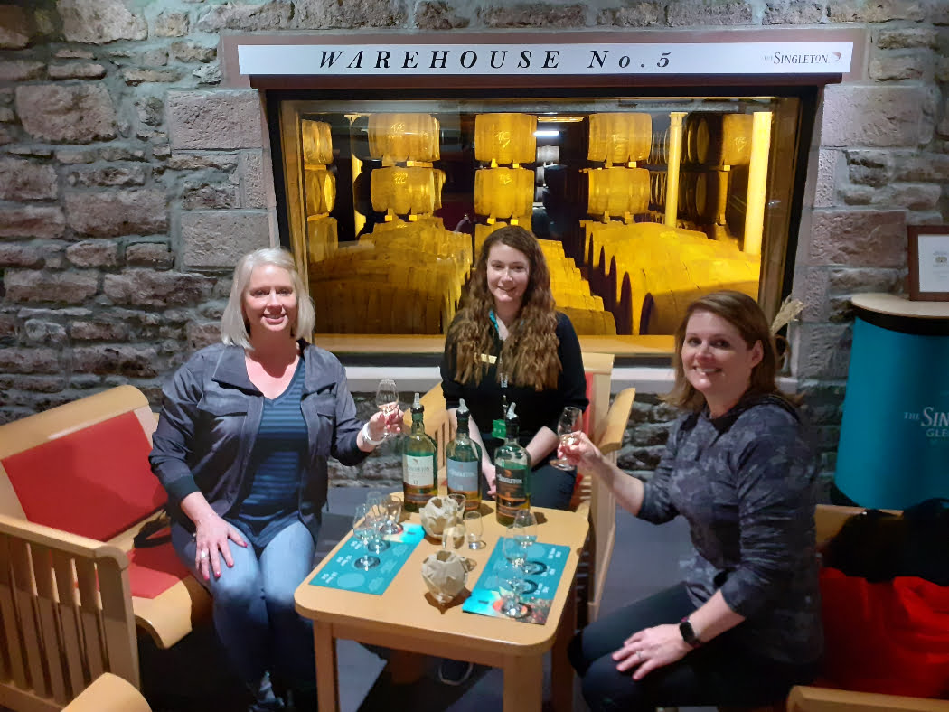 Three women sit at a table, with glasses and three bottles of whisky. Two are in the act of toasting, and the one at the back of the table (in the middle) has no glass and appears to be a badged guide. Behind them is a stone wall with a window, giving a view into a lit whisky-barrel warehouse.