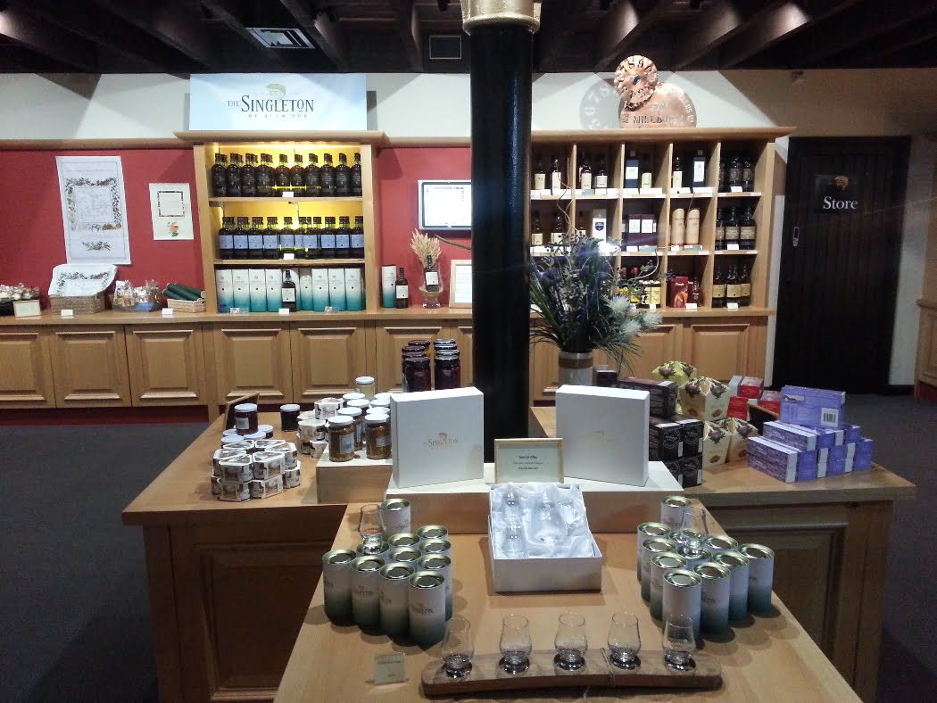 A distillery shop, well lit, carpeted, with pine shop fittings and one central pillar. Merchandise on shelves includes bottles of whisky, glasses, jams and fudge.