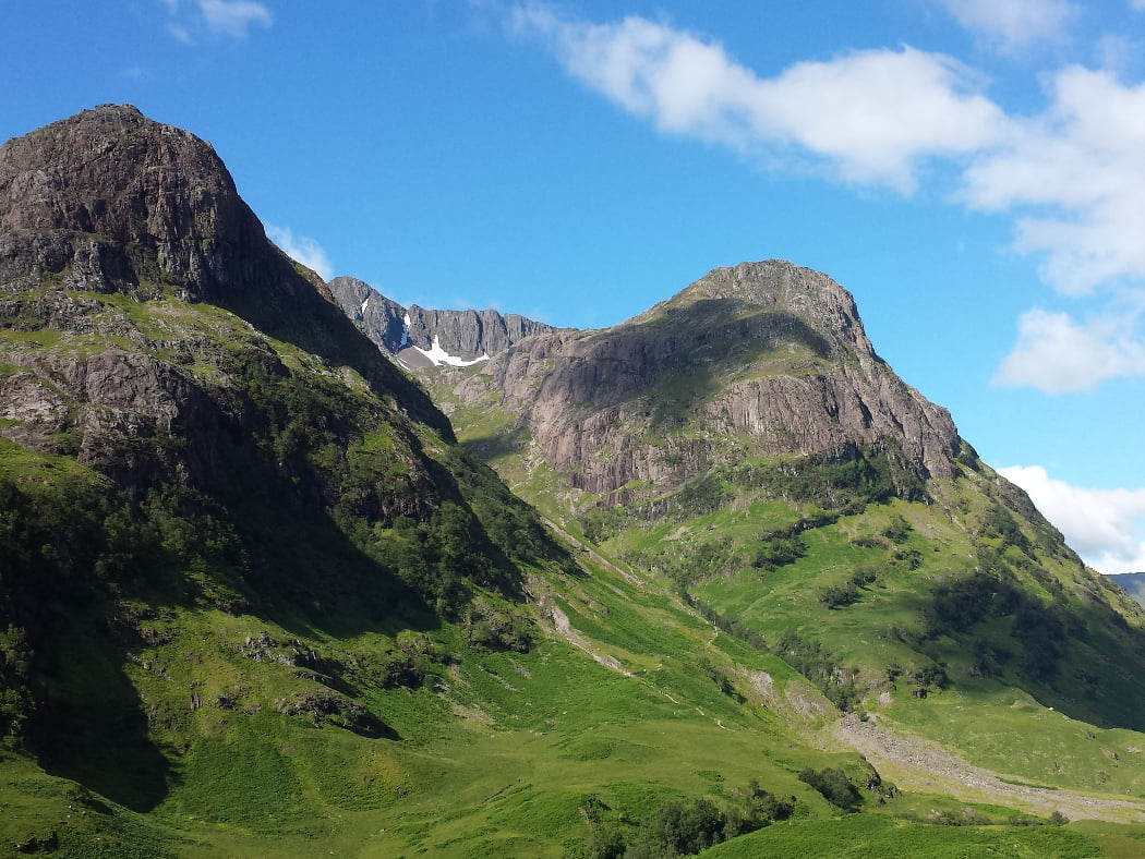 Two mountains in Glencoe on our Fort William and the Scenic Glens Tour. The mountains summits are domed, dark and rocky, and connected by a narrow rock ridge with some snow lingering in the crevices. The lower slops are green grass and green ferns, and all under a blue sky.