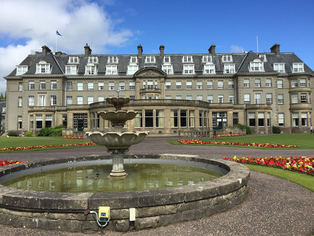Gleneagles Hotel is a large 1920's luxury hotel in the style of a French Chateau, and it fills the shot right to left. Above is a cloudy blue sky, and in the foreground is a three-tier plain stone fountain.