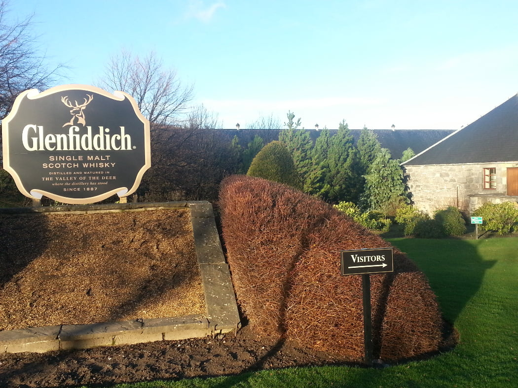 Under a pale blue sky we see an empty raised flower bed and behind it a large sign reading - Glenfiddich Single Malt Whisky, which is a distillery on the Highland and Speyside Distillery Tour. There is a little manicured hedging, shrubs and trees in the background, and a single storey old stone building just coming into view on the right.