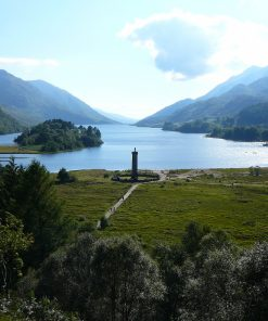 Fort William and the Scenic Glens Tour visits Glenfinnan, the slender stone tower with statue of kilted Highlander on top. Behind the tower a narrow lake disappears into the distance between tall mountains clothed in some native woodland.