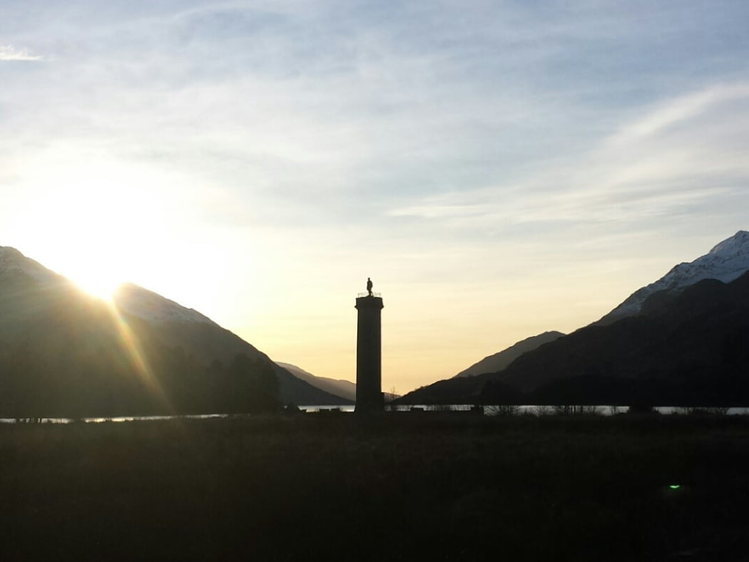 The foreground is dark. The sun is midway through setting behind a high snow-capped mountain to the left. There is a high snow-capped mountain to the right too, and in the v between them lies a lake leading deep into the picture. The focus and centre of the image is a silhouetted tower with a statue of a man on top. The sky is pale yellow at the lake and become bluer with wispy clouds the higher it goes.