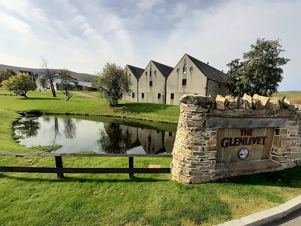 Across a low 2-rail timber fence to the left is grass, and a pond reflecting the three warehouse that stand just beyond. In the foreground to the right is an ornamental wall with a large sign mounted that says The Glenlivet. There are half a dozen individual trees around the grounds and warehouses. Back left are a distant complex of larger buildings, and behind them rise some far away hills. Distillery