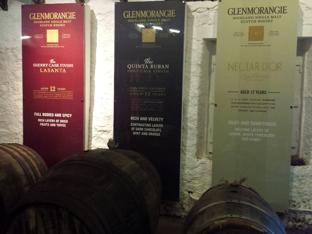 There are three 6 foot tall advertising boards which each describe a different whisky from Glenmorangie Distillery on our Highland Distillery Tour from Inverness. We are inside a warehouse, and in the foreground, on their sides are three barrels, one at the foot of each advertising banner.