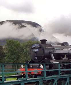 The Jacobite train crossing a bridge (right to left) ,below a cloudy mountain on Inverness Tours' Harry Potter in the Highlands Tour. A ruined castle can be glimpsed among mature trees in the left background.