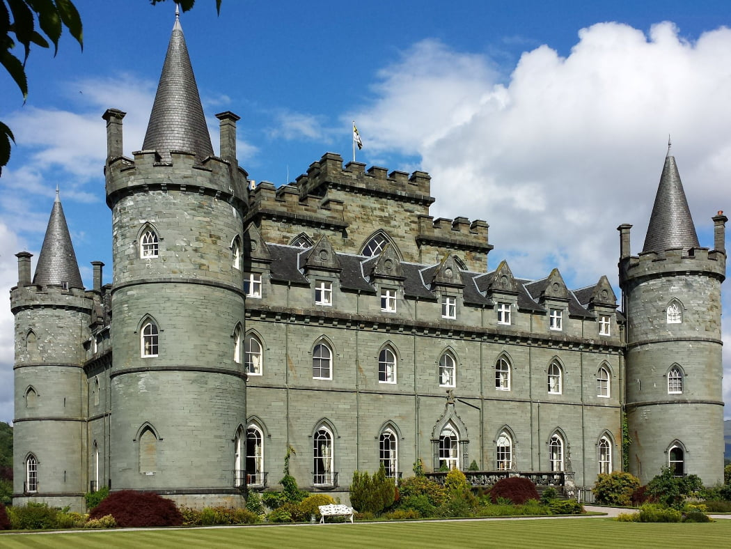 Inveraray Castle on our Loch Lomond and Inveraray Castle Tour dominates and fills this shot. A gothic revival castle built in the 1700's, it is grey, square and with four round corner towers with conical roofs. Green lawns are at the foot of the picture and a cloudy blue sky above.