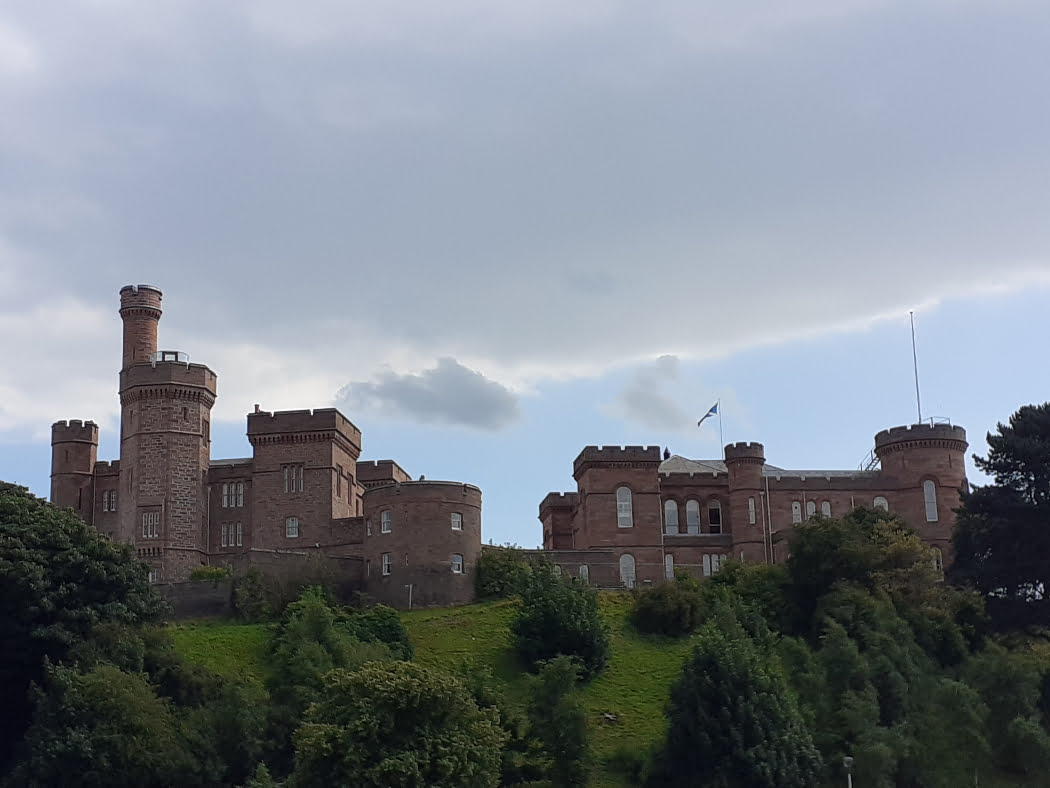 The many sandstone towers of Inverness Castle, on the Old Inverness Walking Tour, are at the top of a small grassy hill. The castle occupies almost the whole image, right to left. There are trees on the grassy bank below it, and a cloudy grey sky above. It is a relatively new castle, dating from the mid-1800's.